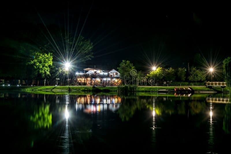 Cafes ljus vid sjön nattetid royaltyfri bild