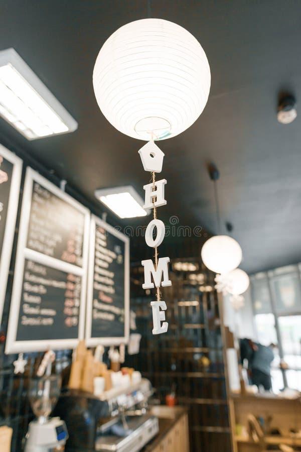Cafetaria moderna, interior, contador da barra, foco na lâmpada redonda branca do papel e a casa da palavra em letras de madeira  fotografia de stock