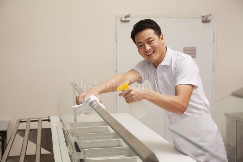 Cafetariaarbeider het schoonmaken voedsel dienend gebied royalty-vrije stock fotografie