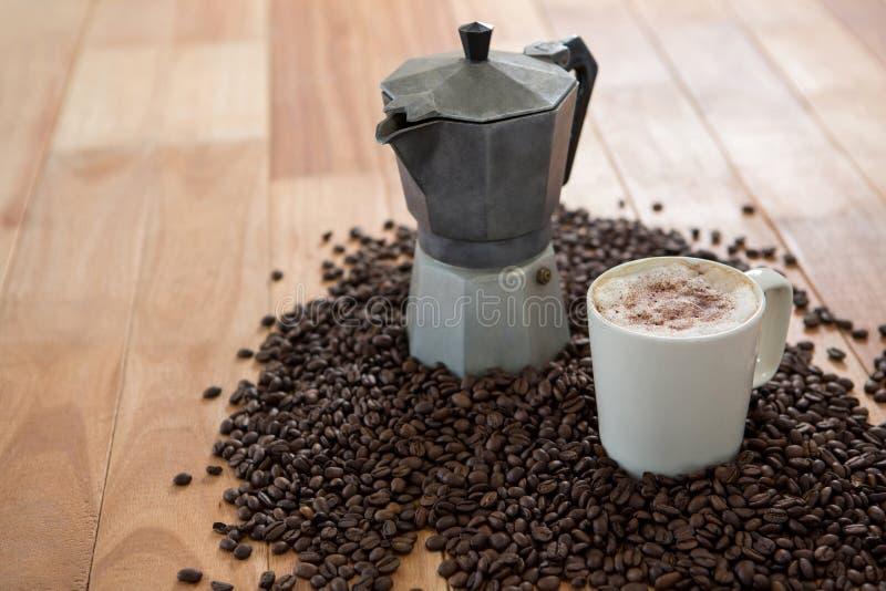 Cafetera con los granos de café y la taza de café imagenes de archivo