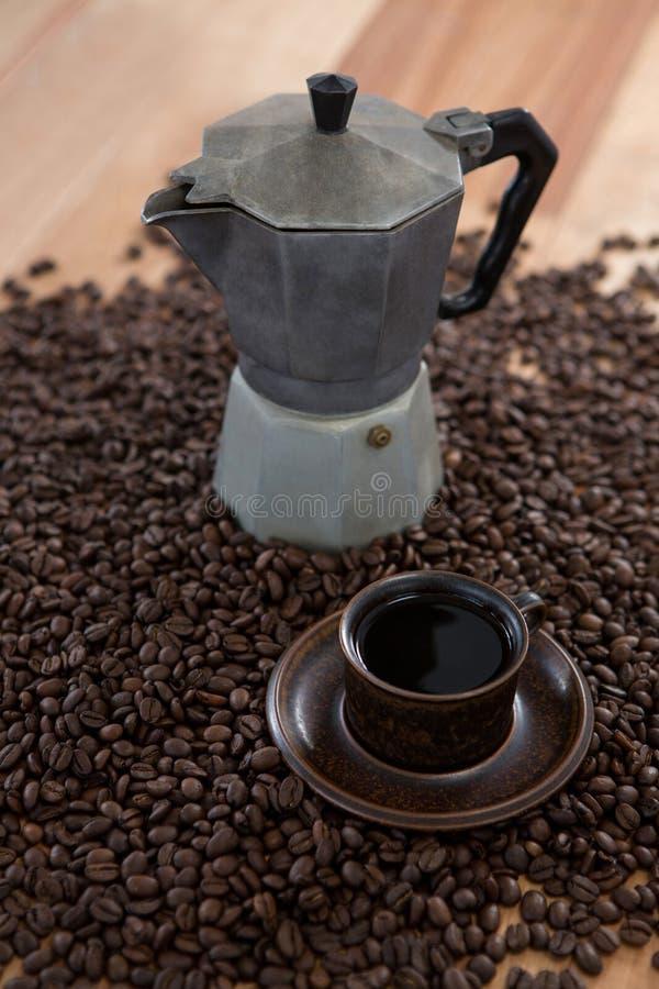 Cafetera con los granos de café y la taza de café foto de archivo