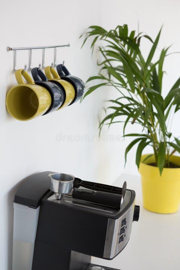 Cafetera, planta de tiesto y tazas colgando en el gancho foto de archivo