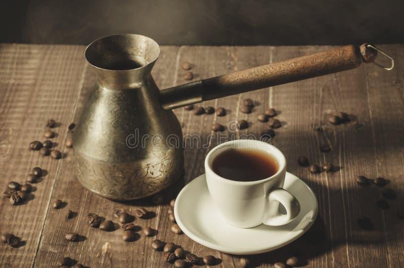 cafetera y taza blanca con café con vapor caliente en un de madera imagen de archivo