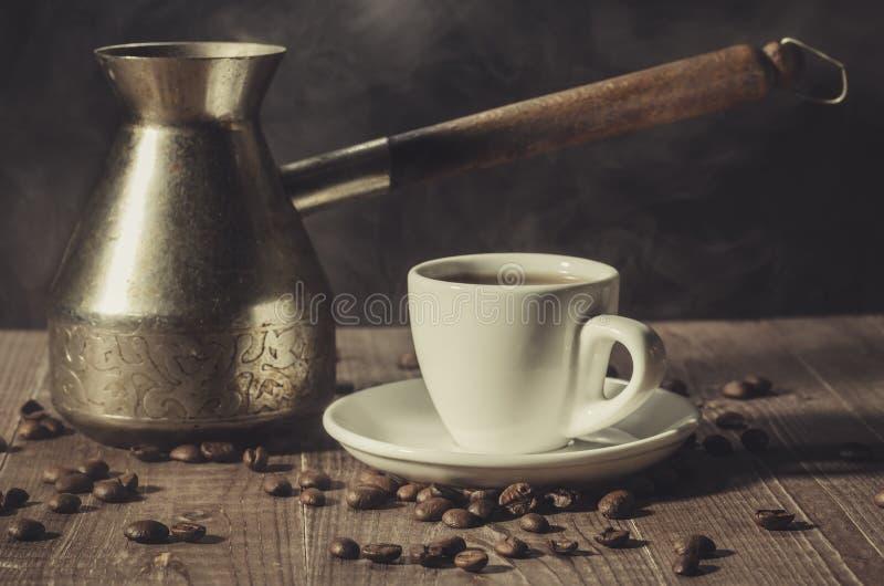 cafetera y taza blanca del café en un fondo/un cof de madera imagenes de archivo