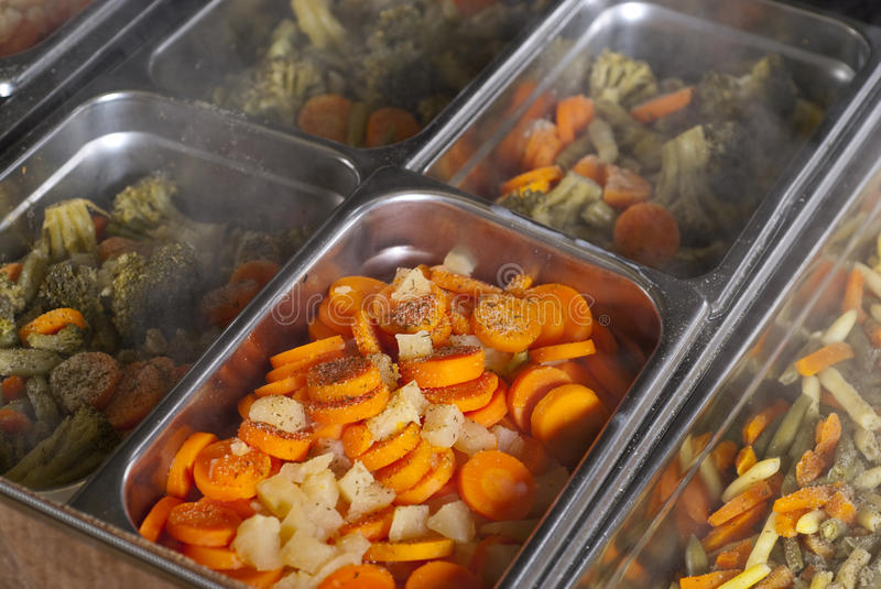 Cafeteria food. In silver containers. carrots, broccoli, peas, green beans,onions stock image