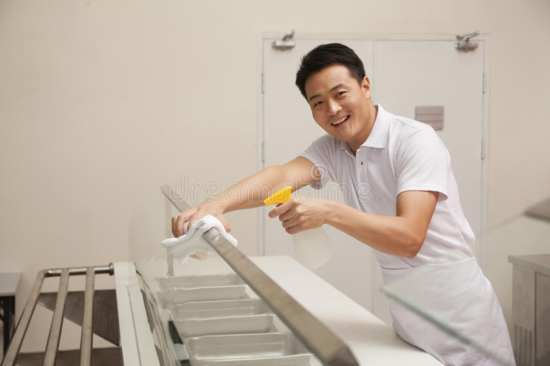 Cafeteria worker cleaning food serving area royalty free stock photography