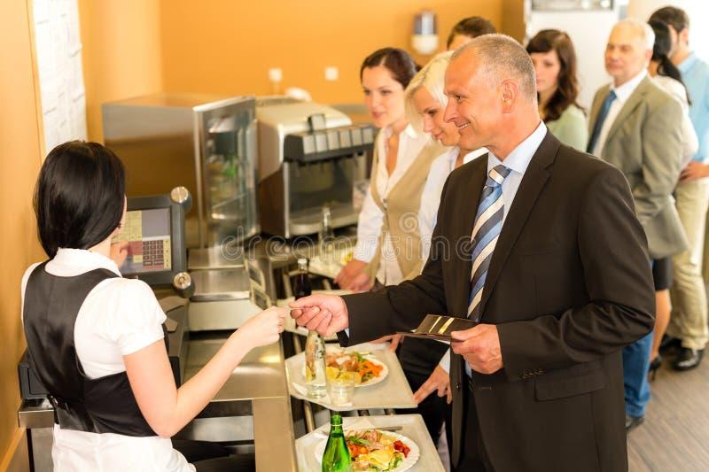 CafeteriaGeschäftsmanlohn durch Kreditkartekassierer lizenzfreies stockfoto