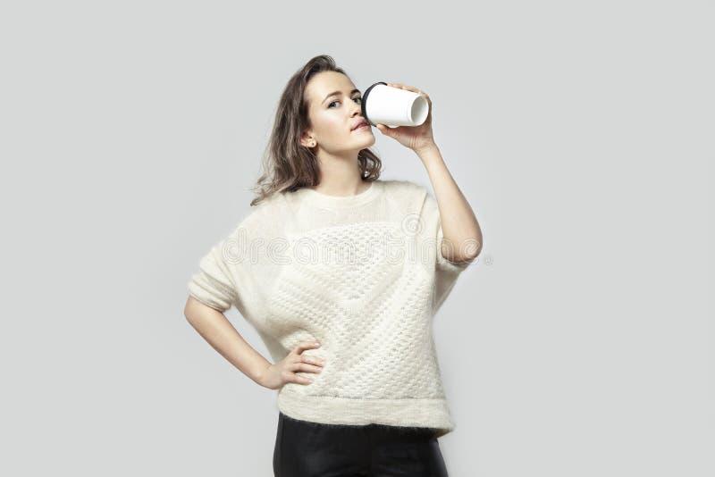 Caffè bevente d'uso del maglione bianco della bella donna bionda dei pantaloni a vita bassa dalla tazza di carta Pacchetto da por fotografia stock