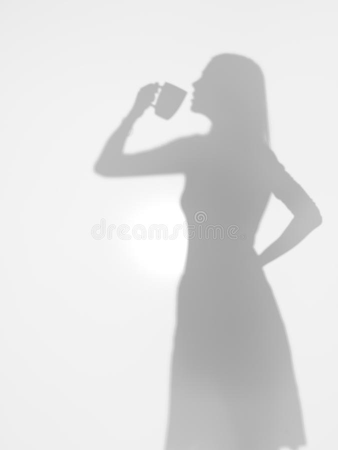 Caffè bevente da una tazza, siluetta della donna fotografia stock