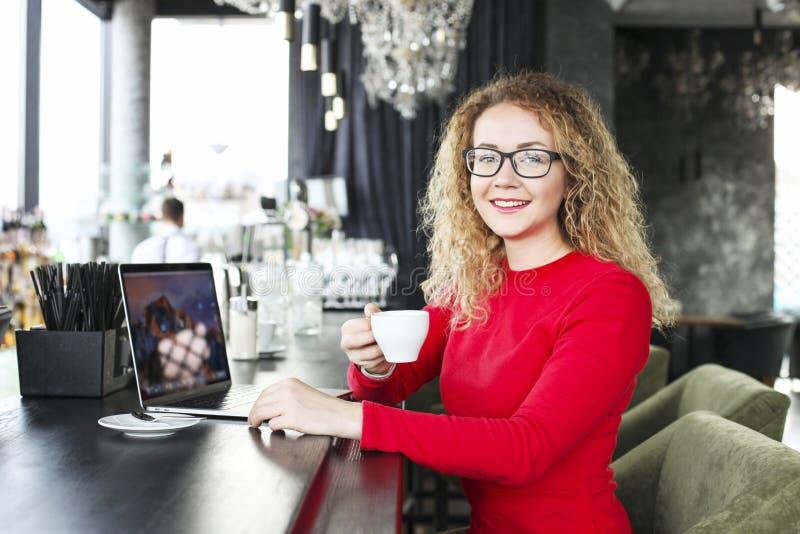 Caffè bevente del cappuccino della bella giovane donna bionda in una barra ed in un sorridere dei pantaloni a vita bassa Blogger  fotografie stock libere da diritti