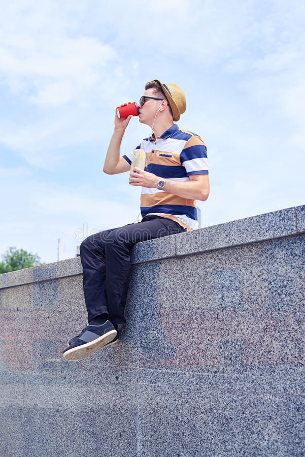Caffè bevente del giovane tipo di modo mentre pranzando all'aperto fotografia stock