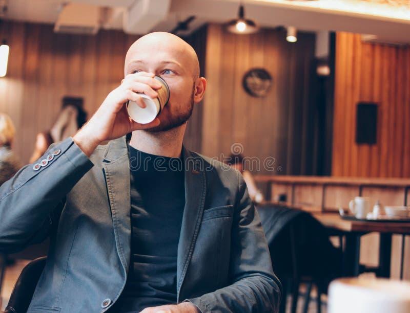Caffè bevente dell'uomo calvo adulto dalla tazza di carta ed esaminare nella finestra il caffè immagine stock