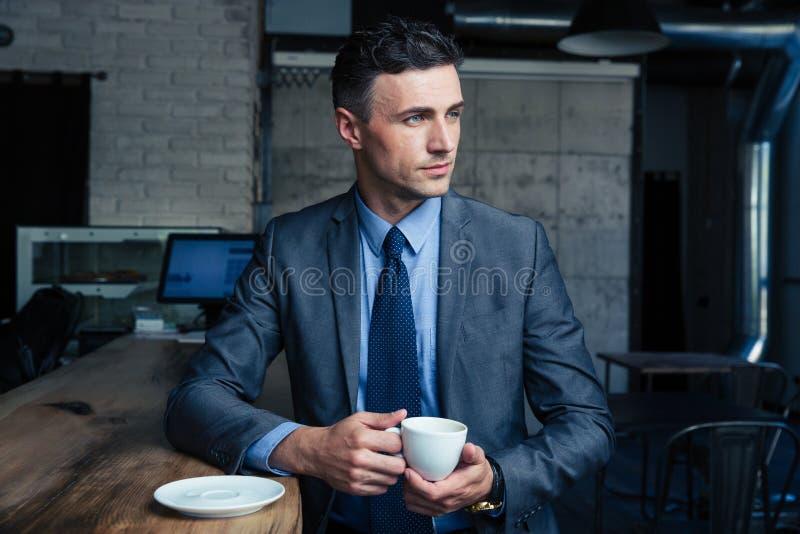 Caffè bevente dell'uomo d'affari bello in caffè fotografie stock