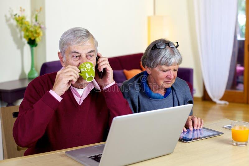 Caffè bevente dell'uomo senior mentre sul telefono fotografia stock