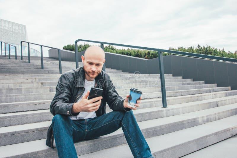 Caffè bevente dell'uomo triste calvo adulto dalla tazza e dal utilizzare di carta seduta del telefono cellulare nelle scale alla  fotografia stock
