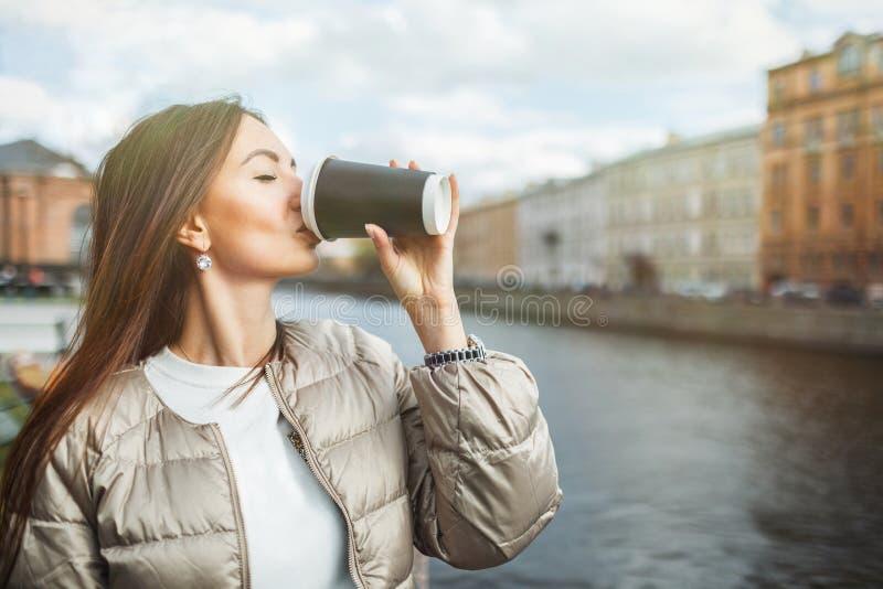Caffè bevente della bella ragazza da una tazza di carta sui precedenti di vecchia città Con lo spazio della copia per testo fotografie stock libere da diritti