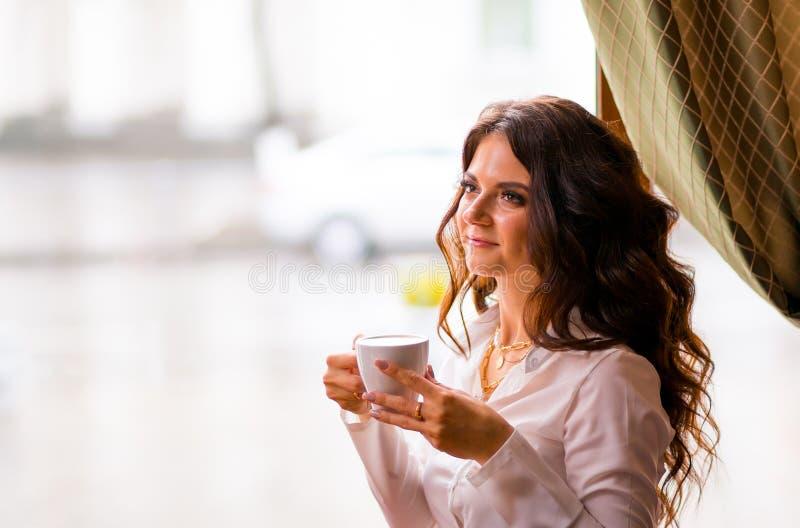Caffè bevente della donna castana alla moda felice in un caffè ed in un sorridere fotografie stock