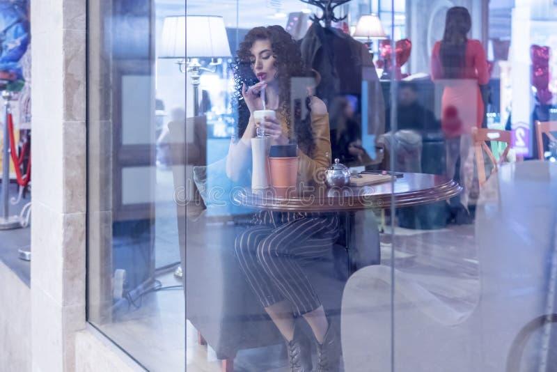 Caffè bevente della donna da una paglia fotografia stock