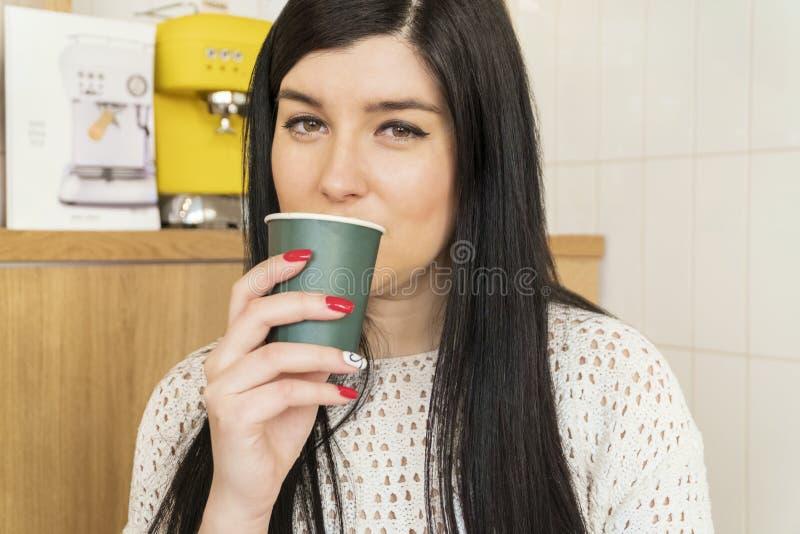 Caffè bevente della donna da una tazza di carta immagine stock