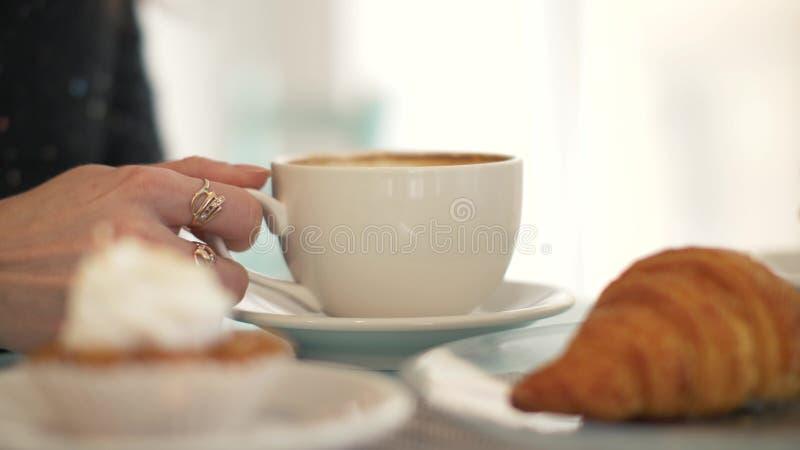 Caffè bevente della donna dalla tazza bianca alla tavola nella fine del caffè del forno su immagini stock libere da diritti