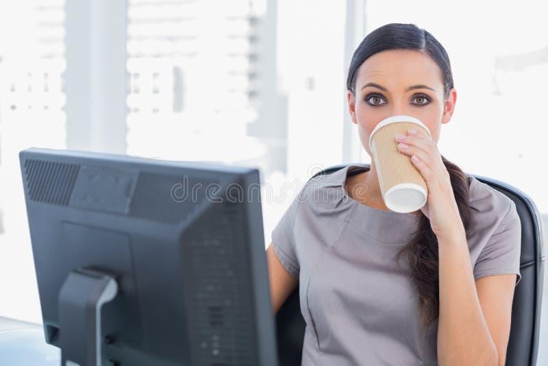 Caffè bevente della donna di affari attraente ed esaminare macchina fotografica fotografia stock libera da diritti