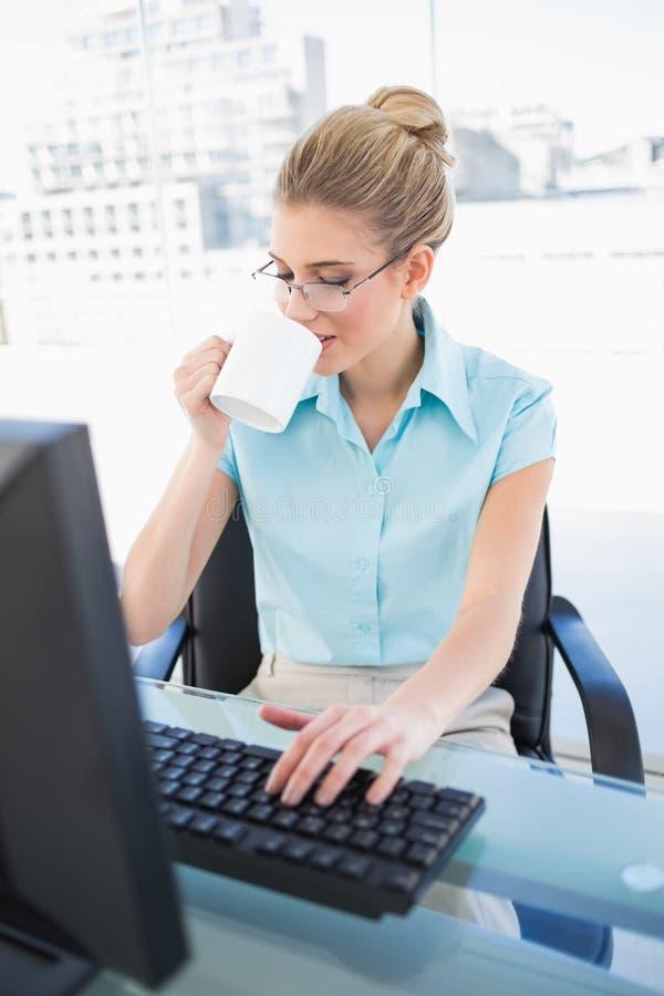Caffè bevente della donna di affari elegante pacifica mentre lavorando immagini stock libere da diritti