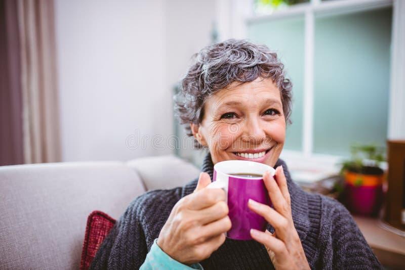 Caffè bevente della donna matura felice a casa fotografia stock libera da diritti