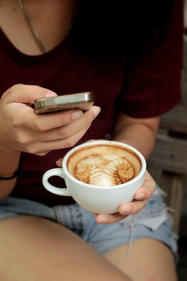 Caffè bevente della donna in tazza e Smart Phone immagine stock