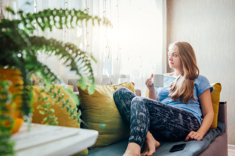 Caffè bevente della giovane donna che si siede nel salone immagine stock