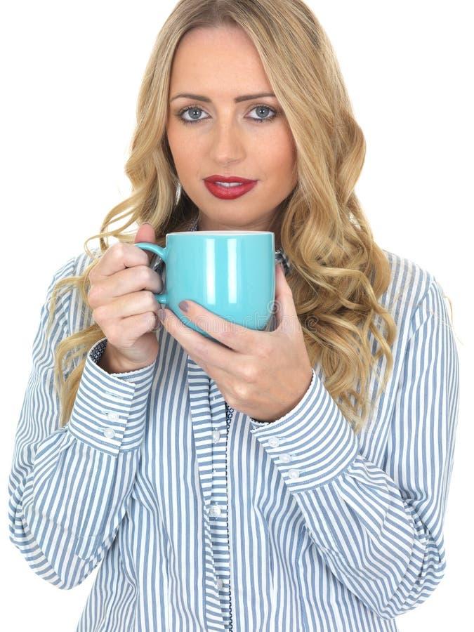 Caffè bevente della giovane donna da una tazza blu immagine stock
