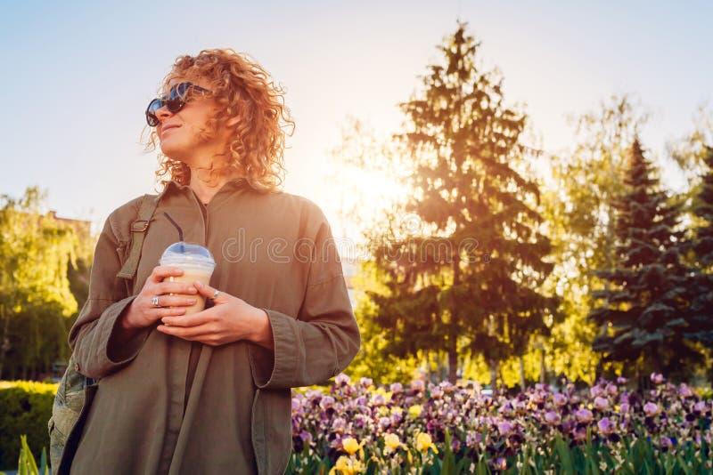 Caffè bevente della giovane donna dei pantaloni a vita bassa contro mentre aspettando gli amici Ragazza alla moda di estate nel r immagini stock