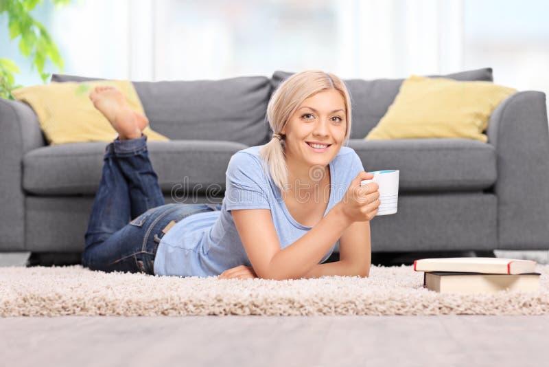 Caffè bevente della giovane donna e trovarsi sul pavimento immagine stock libera da diritti