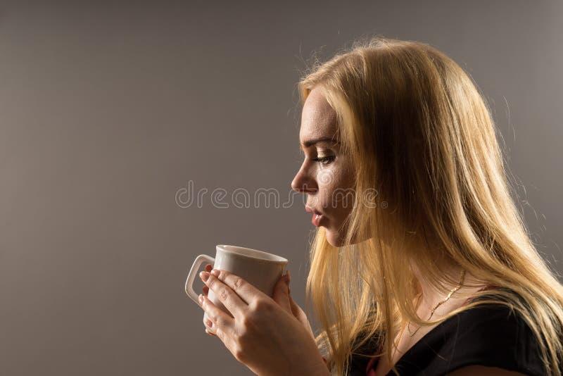 Caffè bevente della giovane donna Ragazza bionda con la tazza di tè bianca su un fondo grigio immagine stock