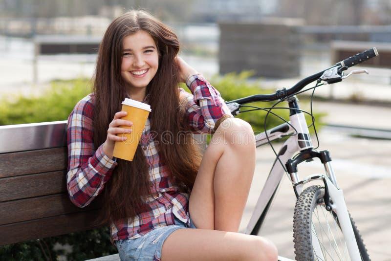 Caffè bevente della giovane donna su un viaggio della bicicletta fotografia stock