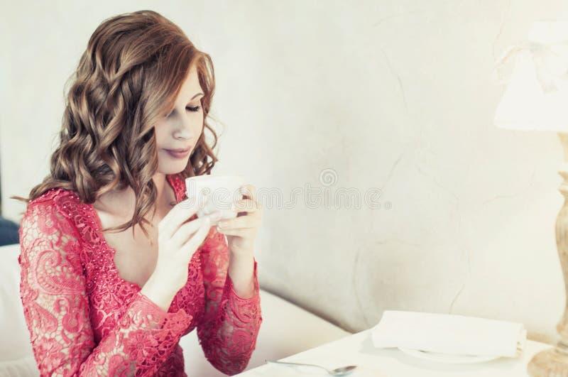 Caffè bevente della giovane donna in un caffè fotografie stock