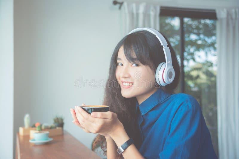 Caffè bevente della ragazza mentre musica d'ascolto fotografia stock