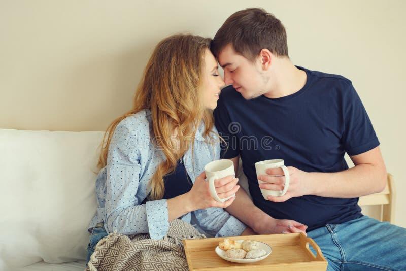 Caffè bevente delle giovani coppie a letto fotografia stock
