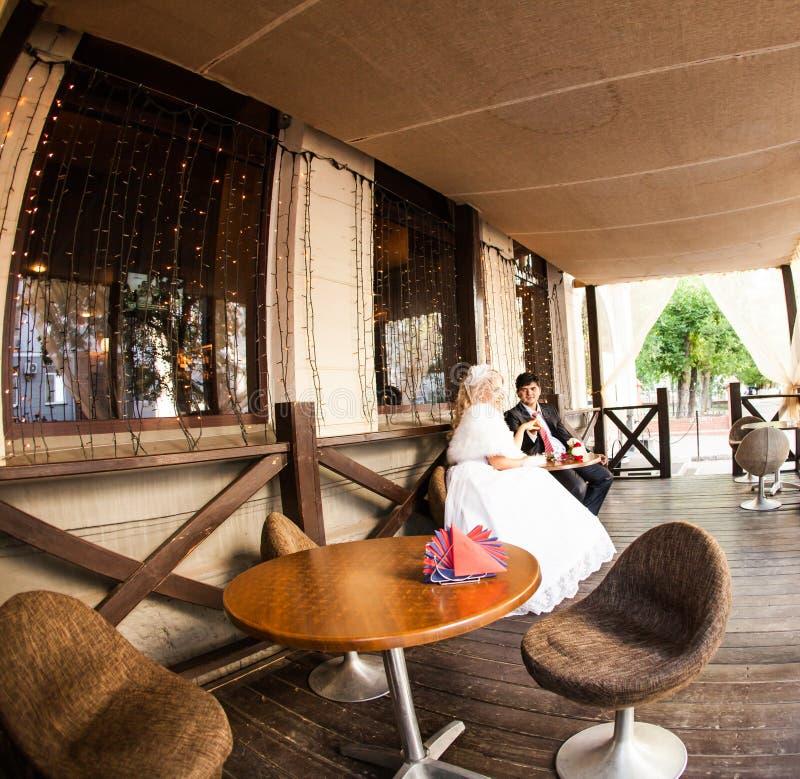 Caffè bevente dello sposo e della sposa ad un caffè all'aperto immagine stock
