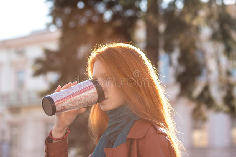 Caffè bevente di bella signora della testarossa dalla chiavetta immagine stock