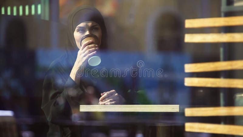 Caffè bevente di signora araba graziosa in caffè, guardante nella finestra, cultura islamica immagine stock libera da diritti