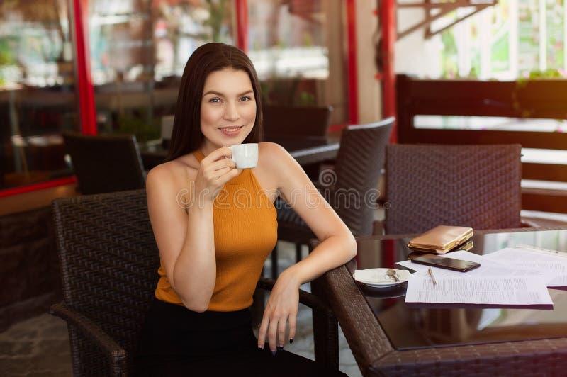 Caffè bevente felice della donna di affari con le carte sparse sulla tavola buone notizie, gioia e felicità fotografia stock