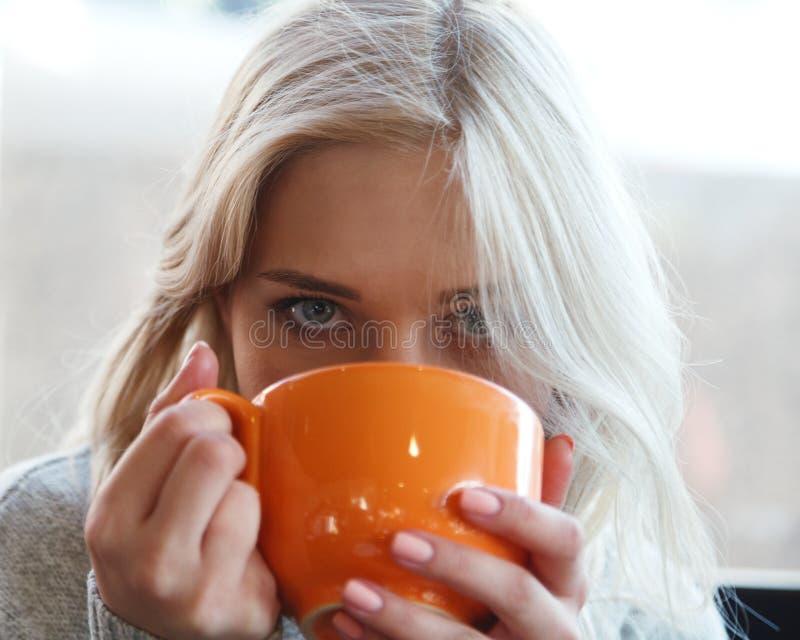 Caffè bevente o tè della bella giovane donna bionda da una tazza arancio Primo piano del caffè bevente della donna dentro il caff fotografie stock libere da diritti