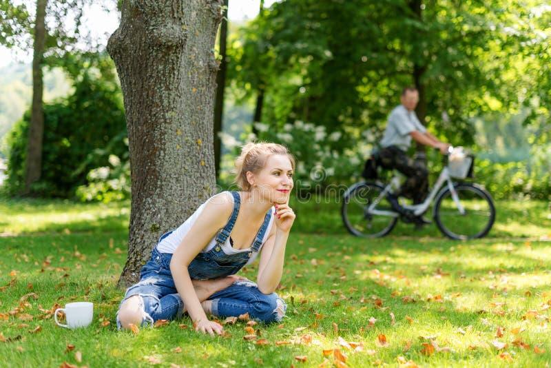 Caffè bevente o tè della giovane donna bionda nella foresta che gode del tempo caldo in autunno fotografie stock
