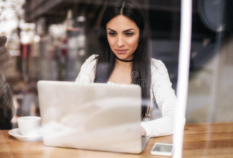 Caffè bevente sorridente della donna e praticare il surfing su Internet Vento del caffè immagini stock libere da diritti