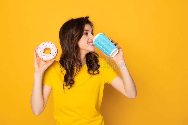 Caff? bevente sorridente felice della ragazza con la ciambella fotografia stock