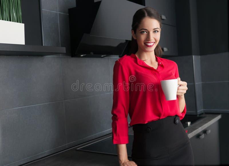 Caffè bevente/tè della bella donna di affari in una cucina moderna fotografie stock