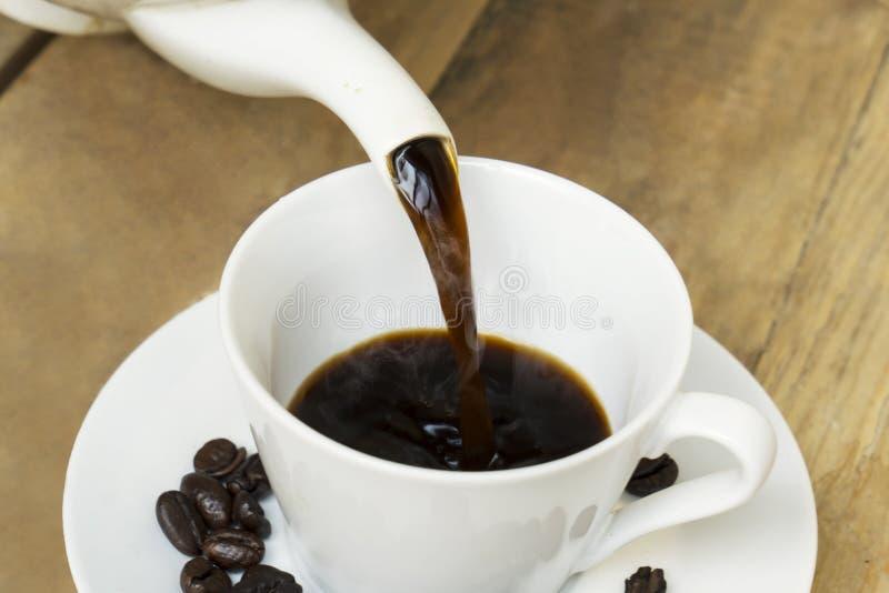 Caffè caldo che versa nella tazza sulla tavola di legno immagine stock