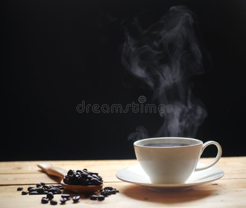 Caffè caldo con i chicchi caldi di caffè e del fumo sulla tavola di legno fotografia stock