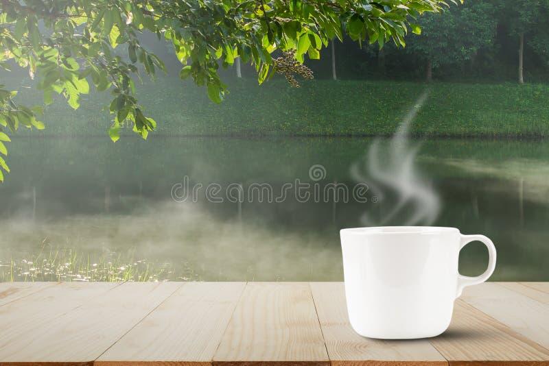 Caffè caldo con vapore sul piano d'appoggio di legno sul fondo nebbioso vago della foresta e del lago fotografia stock