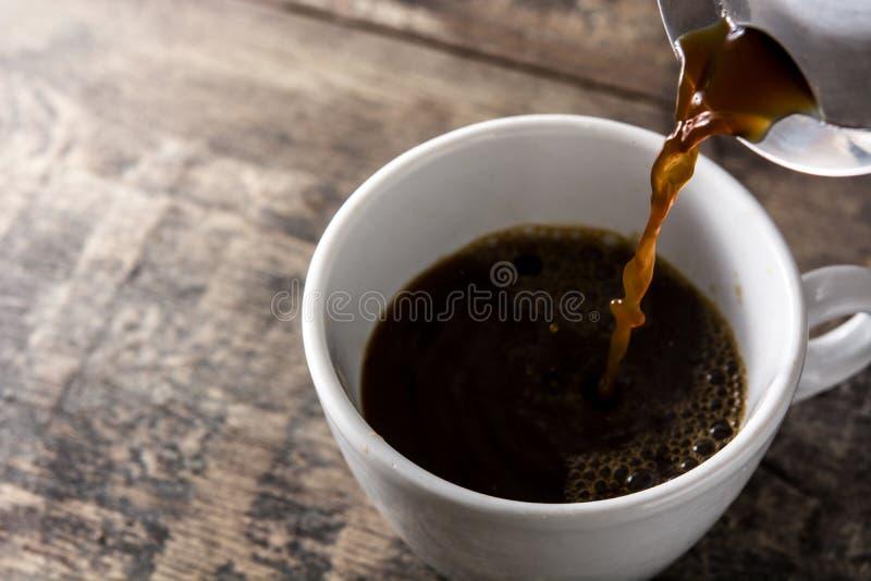 Caffè caldo di versamento in una tazza su legno fotografie stock libere da diritti